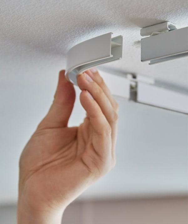 Persona uniendo las piezas de esquina de un sistema de rieles VIDGA de IKEA colocado en el techo.