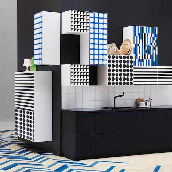 Personnalisez votre cuisine à l'aide des motifs graphiques des portes YTTERBYN de IKEA. La collection propose des façades à motifs uniques sur fond blanc rappelant les années 1970, comme des carreaux bleus, des rayures ou des pastilles noires, entre autres.
