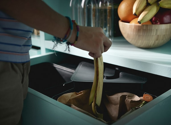 Personne avec des bracelets en train de laisser tomber une peau de banane dans une poubelle de recyclage IKEA VARIERA, dans un tiroir d'une cuisine.