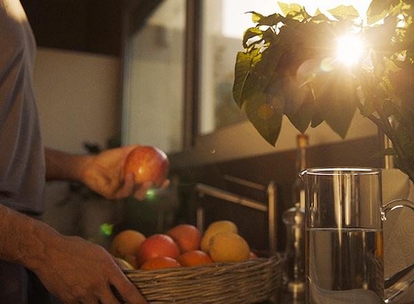 Personne tenant une corbeille de pommes dans les mains avec les rayons du soleil qui traversent les feuilles d'une plante