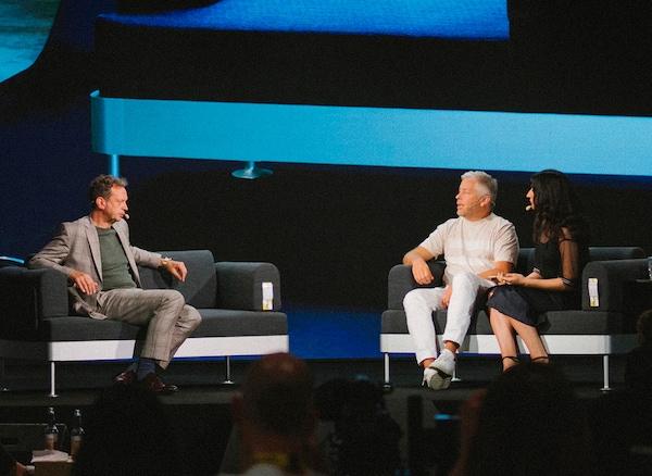 Personnes sur scène avec derrière eux l'image d'un canapé projetée sur un écran.