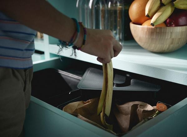 Pertsona bat eskuan eskumuturrekoak daramatzana, platano bat zuritu eta azala sukaldeko kaxoi batean dagoen birziklatzeko IKEA VARIERA edukiontzian azala botatzen duena.