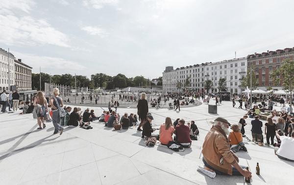 Pessoas numa praça grande com assentos nas laterais e uma zona desportiva no centro.