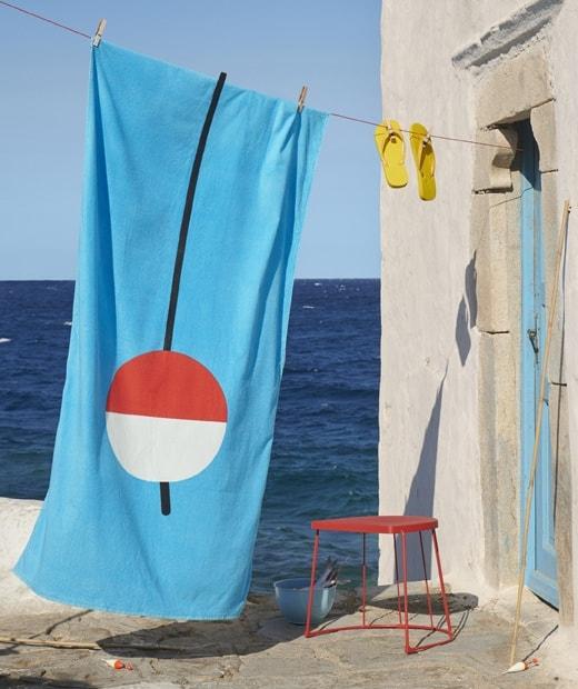 Pestrý plážový uterák a šľapky zavesené na šnúre na bielizeň vedľa červeného príručného stolíka pri mori.