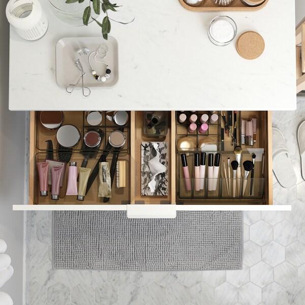 Pesualtaassa on marmoriefekti. Avoimessa laatikossa on GODMORGON-säilytyslaatikot joiden avulla saat järjestettyä meikit kauniisti.