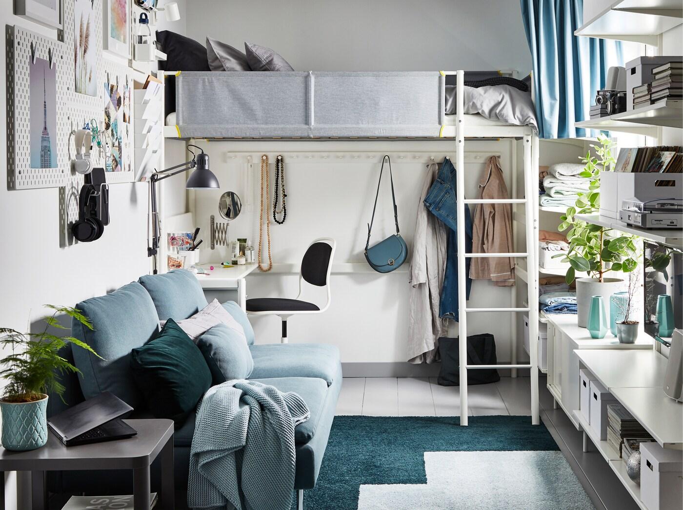 Petit appartement à une chambre dans les tons de gris, vert et blanc. Sous un lit mezzanine se trouve un bureau.