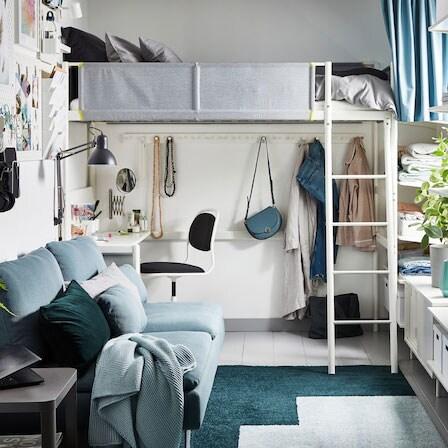 Petit appartement une chambre en gris, vert et blanc, avec lit mezzanine sous lequel est installé un bureau.
