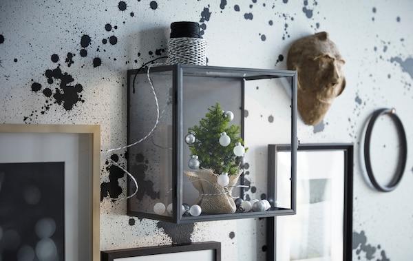 Petit arbre gris argent et décorations blanches placés dans une boîte vitrée.