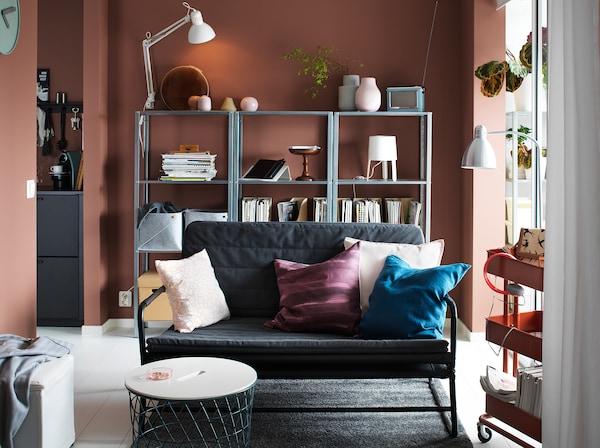 Petit canapé gris foncé dans un salon aux murs couleur rouille avec des étagères devant le mur du fond.