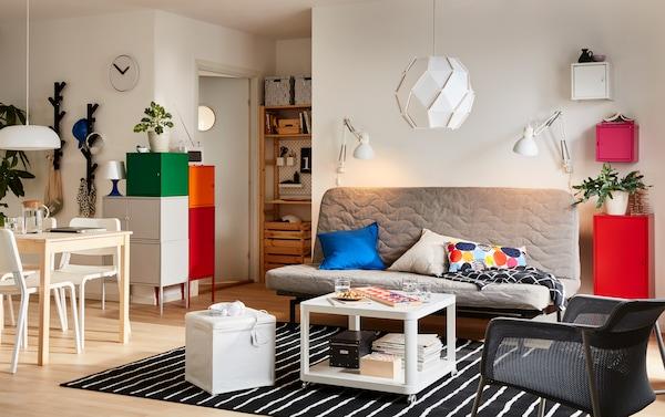 Petit espace de vie ouvert en gris et blanc avec canapé convertible NYHAMN en gris-beige et table à manger en pin INGO.