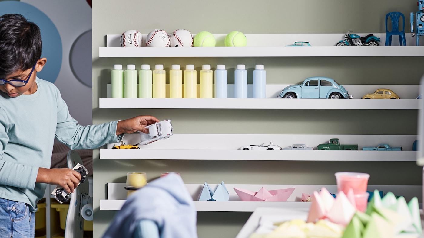 Petit garçon rangeant ses jouets sur quatre étagères pour photos MOSSLANDA blanches fixées au mur: balles, bouteilles, jouets, créations en origami et petites voitures.