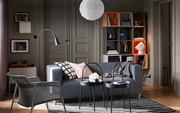 Petit salon gris et orange avec le canapé 2 places KLIPPAN en gris foncé.