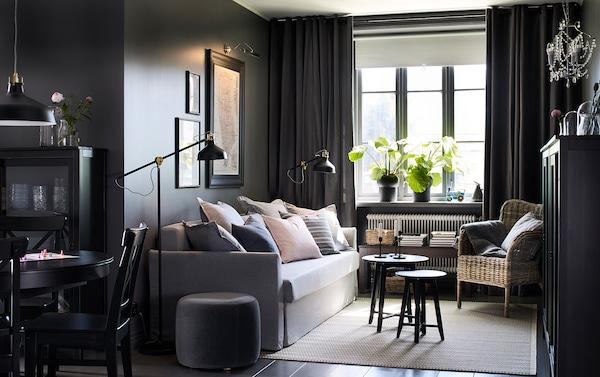 Petit salon-salle à manger gris foncé avec canapé gris.