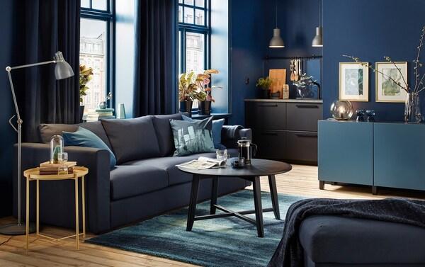 Petit séjour bleu foncé avec canapé noir-bleu et table basse ronde noire.