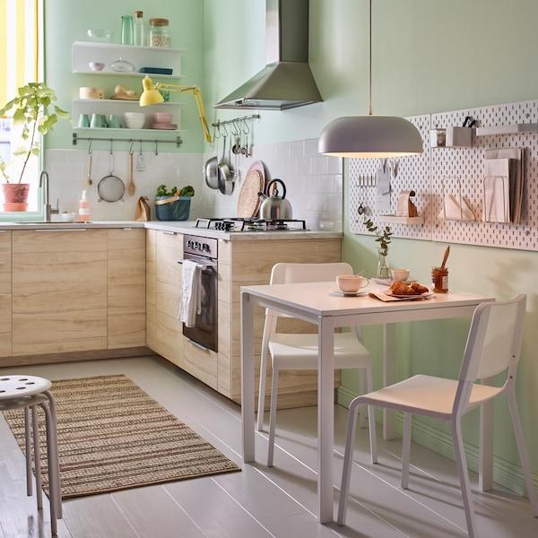 Petite cuisine en beige, vert et blanc avec table MELLTORP et deux chaises empilables TEODORES, le tout en blanc.