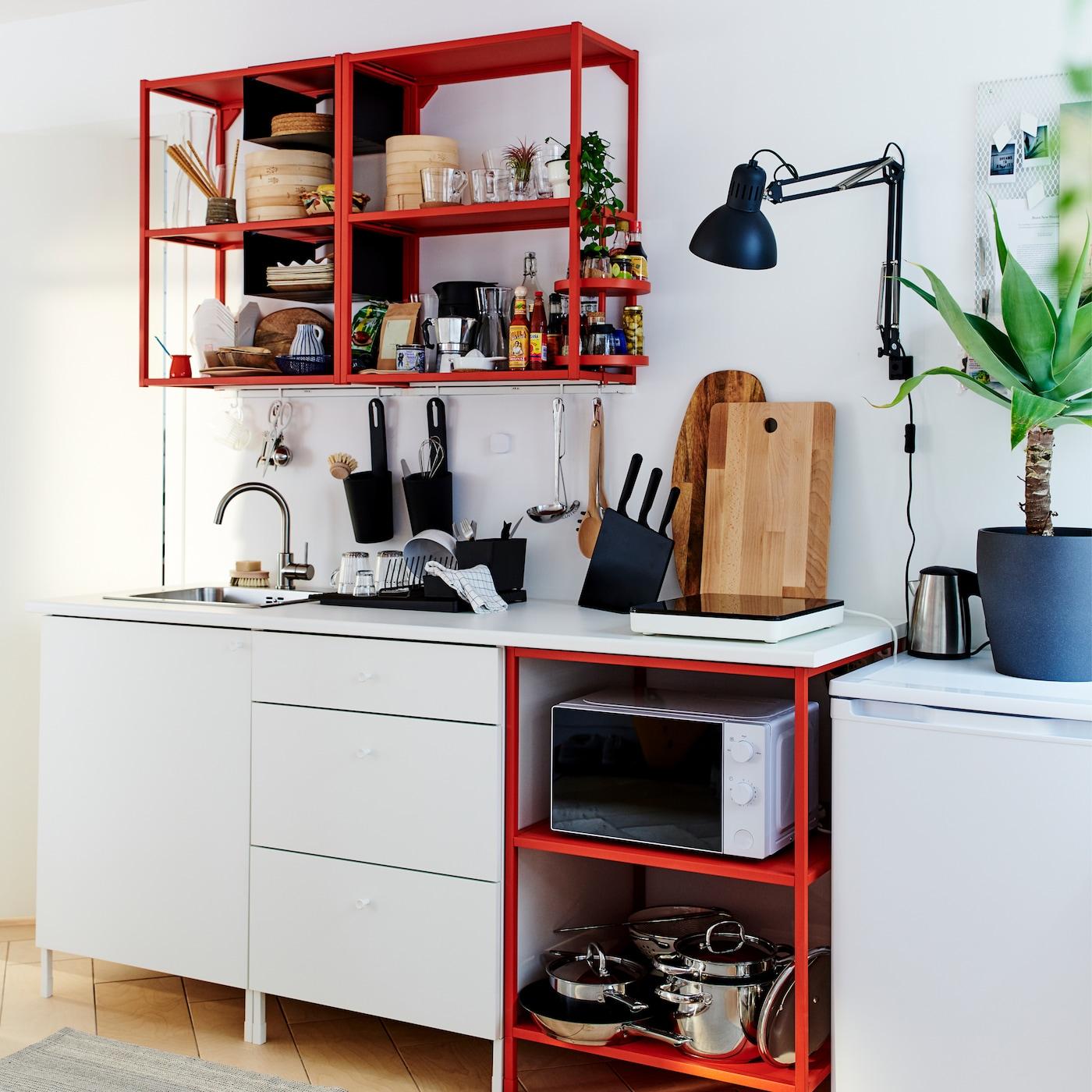 Petite cuisine rouge/blanc avec table à induction mobile, planches à découper en bois, lampe murale et égouttoir en noir.