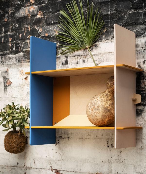 Petite étagère rectangulaire en contreplaqué, sur un mur de briques d'aspect grossier (probablement à l'extérieur).