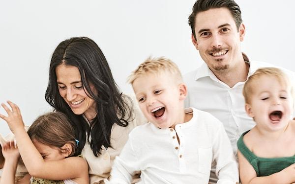 Petočlana porodica se zajedno smeje.