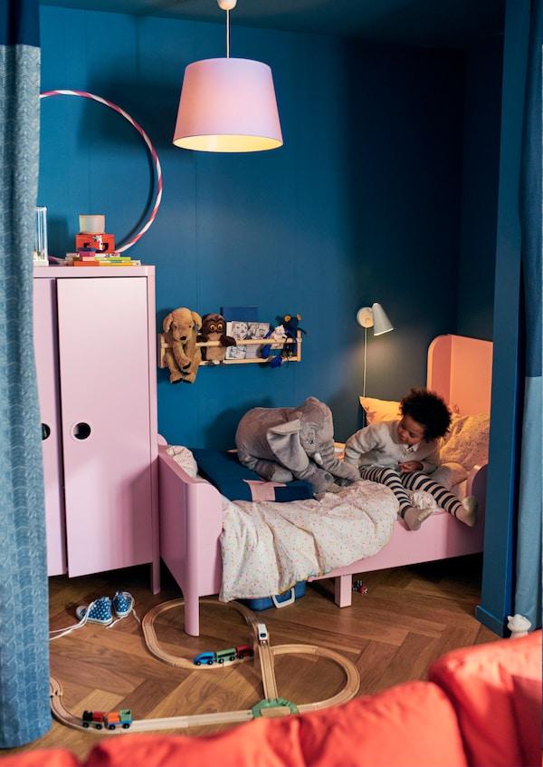 Petroolinsininen ja vaaleanpunainen lastenhuone. IKEA BUSUNGE vaaleanpunainen jatkettava sänky ja vaaleanpunainen BUSUNGE vaatekaappi sopivat jo hyvin pienellekin lapselle.