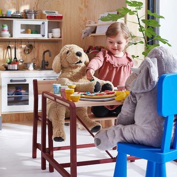 Peuter speelt met haar knuffels aan de YPPERLIG kindertafel | IKEA