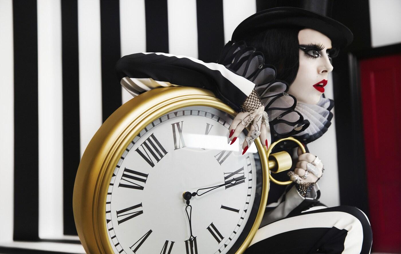 Photo de Bea Åkerlund posant avec une horloge murale.