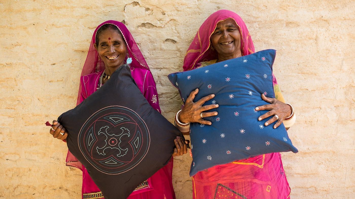 Photo montrant deux entrepreneurs sociaux tenant dans leurs mains le coussin qu'elles ont réalisé. Leurs activités leur permet de s'atteler à des obstacles sociaux et environnementaux, pour réduire la pauvreté et autonomiser les femmes.