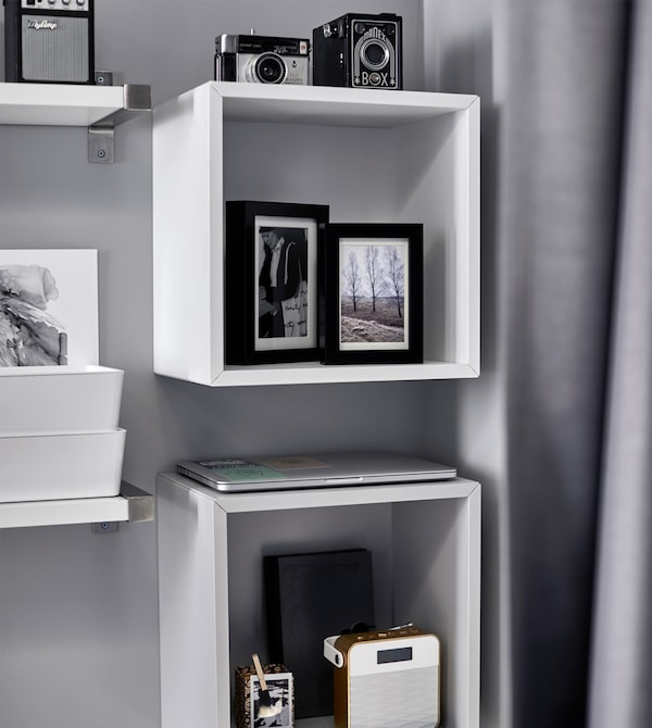 Photos, cameras, and a stereo are displayed on a shelf above a bed.