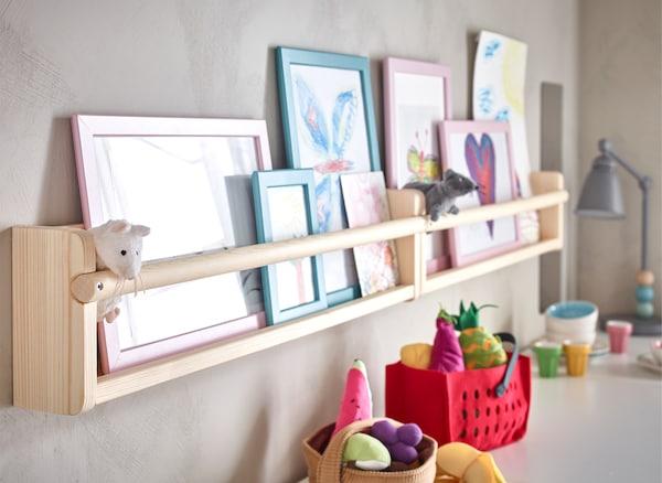Photos et jouets sur deux tablettes juxtaposées.