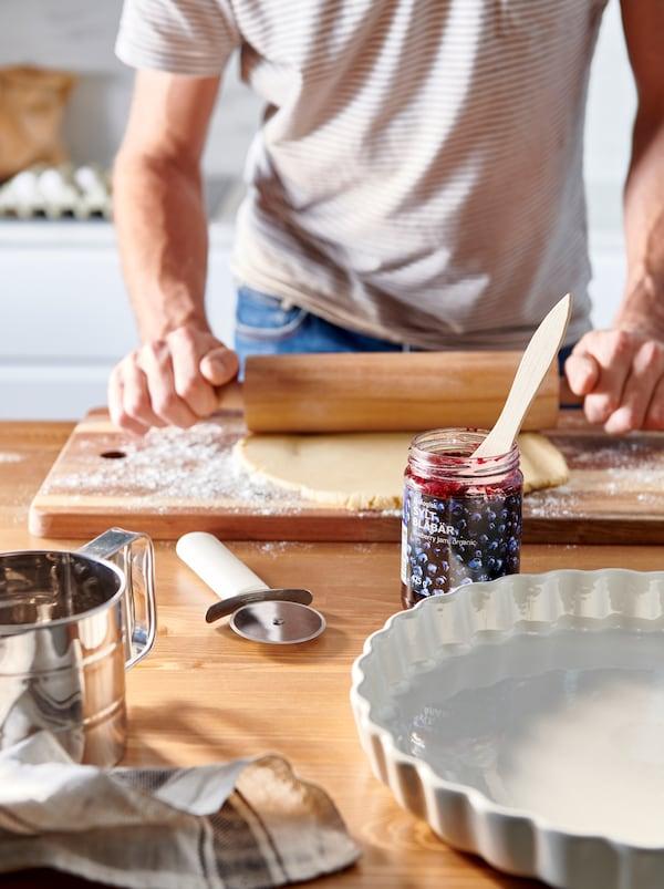 Piano di lavoro con accessori per la cottura in forno e un vasetto di confettura di mirtilli neri SYLT BLÅBÄR. Un uomo lavora una sfoglia di pasta con un mattarello - IKEA