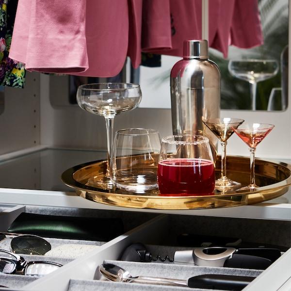 Pića su postavljena na okruglom IKEA GLATTIS poslužavniku mesingane boje s visokom ivicom sa strane.