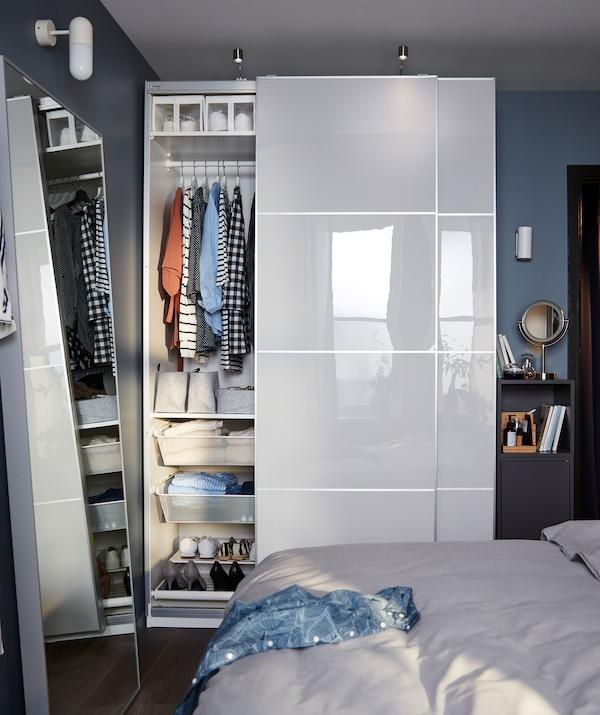 Piccola camera da letto arredata con un armadio PAX ben organizzato e un mobile stretto accanto alla porta - IKEA