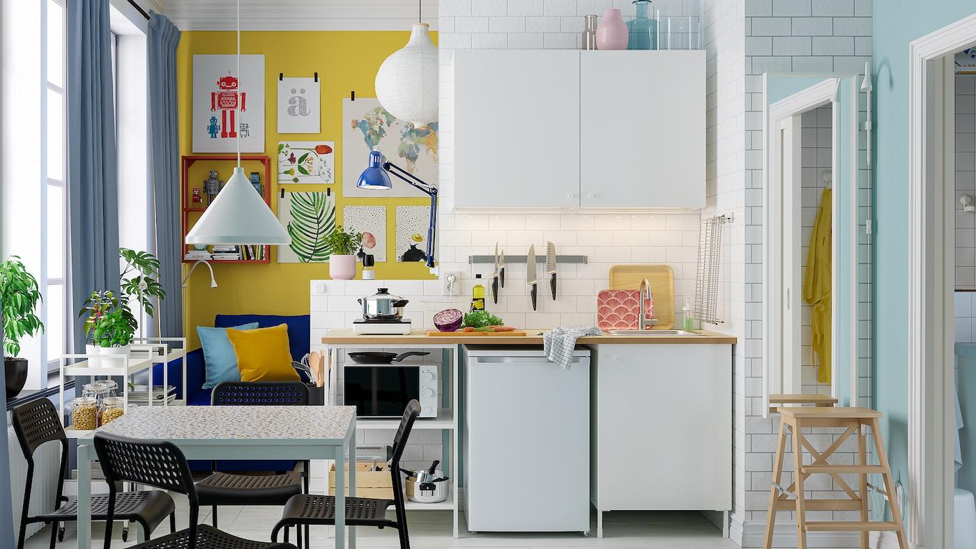 Piccola cucina dai colori chiari con combinazione di mobili ENHET, tavolo da pranzo bianco e quattro sedie nere.