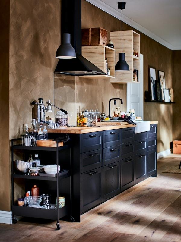 Piccola cucina dotata di ogni funzione, con piccoli pensili a giorno, cappa e frontali cassetti LERHYTTAN scuri.