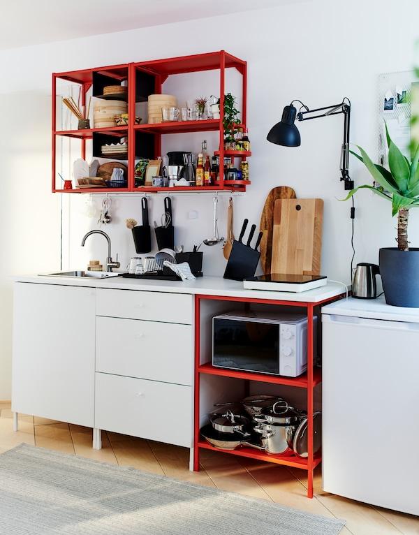Piccola cucina essenziale, con cassetti bianchi, scaffali in metallo rosso a pavimento e a parete, e frigorifero basso.