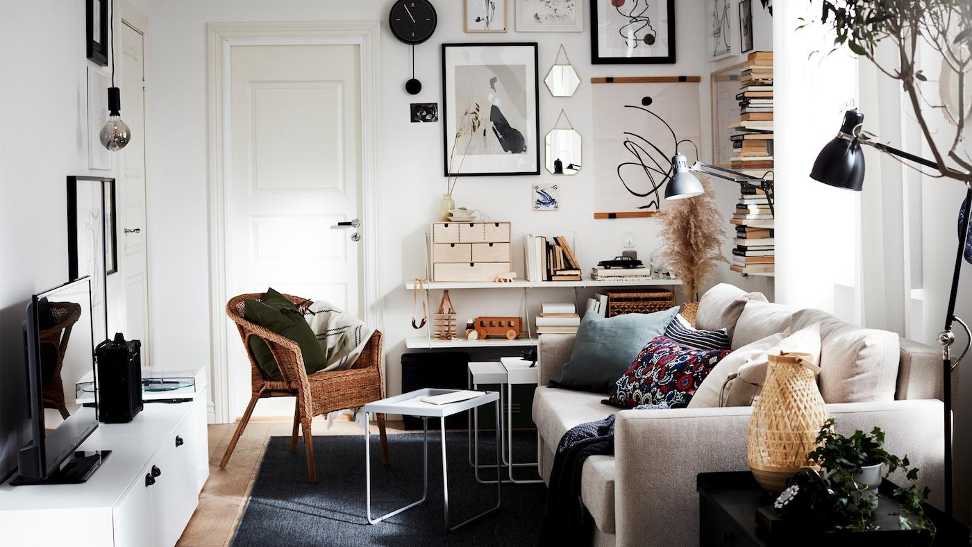 Piccolo soggiorno luminoso con divano, TV, libri ordinati in verticale su mensole e immagini incorniciate su una parete, tutto in colori neutri.
