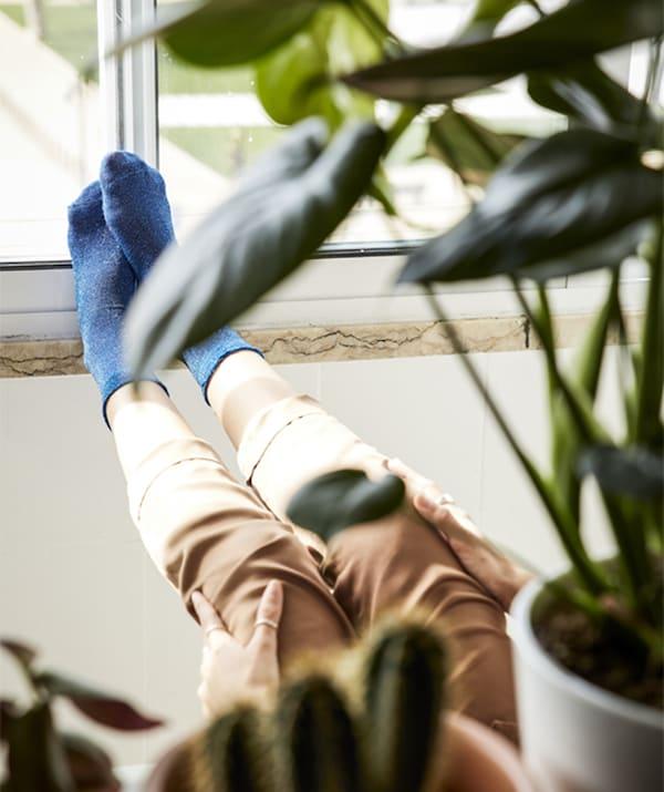 Picioarele unei femei sprijinite de pervaz, văzute printre plantele din ghivece.