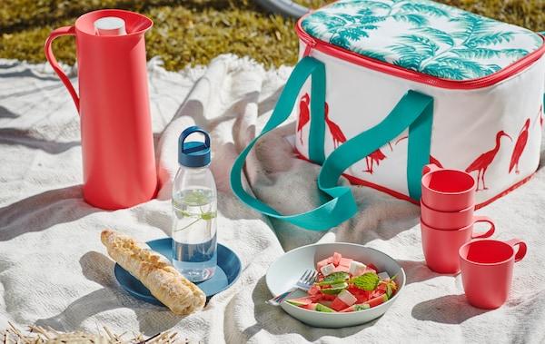 Picnic con coperta bianca distesa sull'erba, apparecchiata con una borsa frigo SOMMARLIV, delle tazze TALRIKA e un'insalata fresca servita in un piatto fondo TALRIKA - IKEA