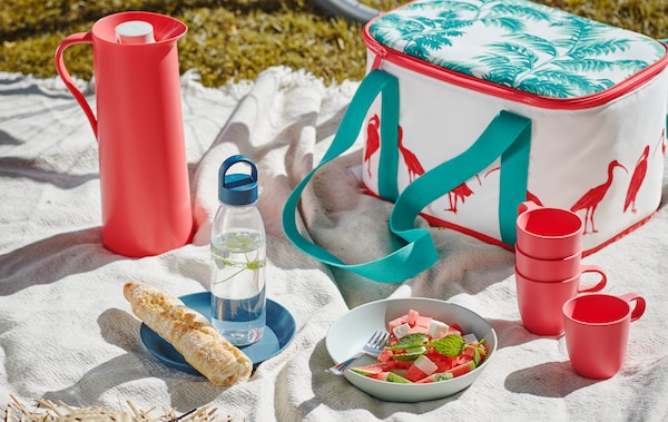 Picnic with a white throw on grass, set with a SOMMARLIV cooling bag, TALRIKA mugs and a summer salad in a TALRIKA plate.