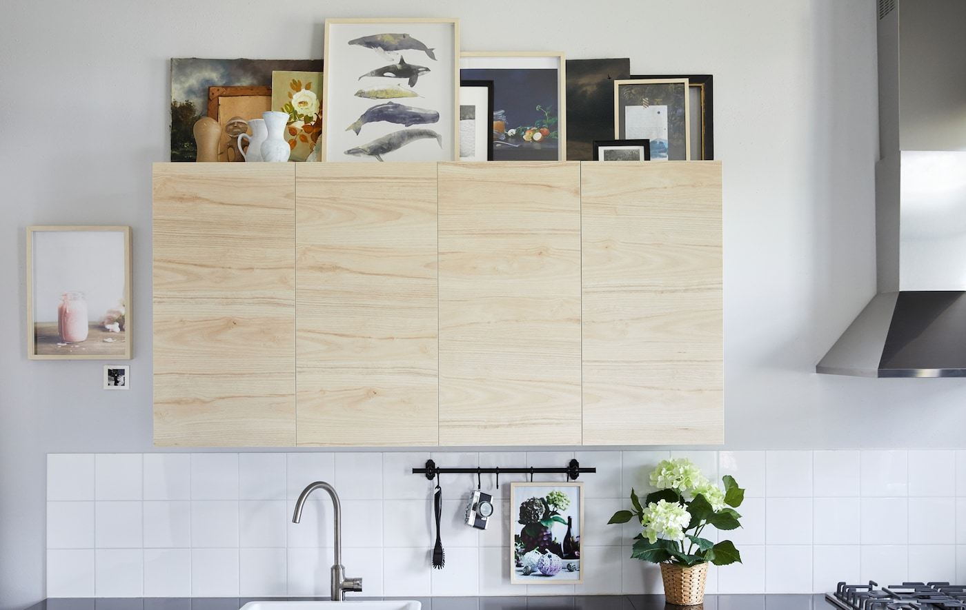 Picture frames and vases arranged on the top of birch kitchen cabinets in a white kitchen with tiled splashback.