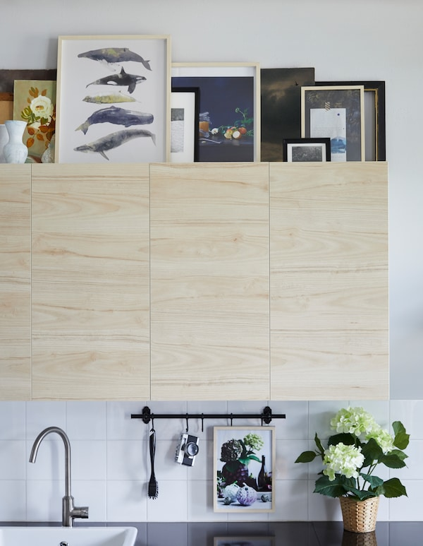 Picture frames and vases arranged on the top of wall cabinets with birch doors in a white kitchen.
