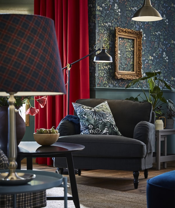 Picture of a dark green armchair with a floral cushion on it and a tartan lamp in the foreground on a side table.