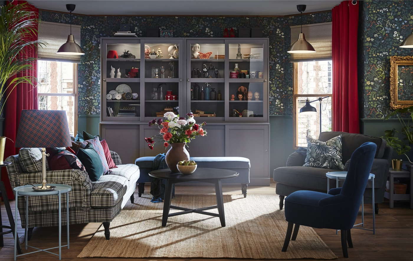 Picture of a living room with sofas, chairs, side tables, floral walls and a large glass-fronted cabinet.