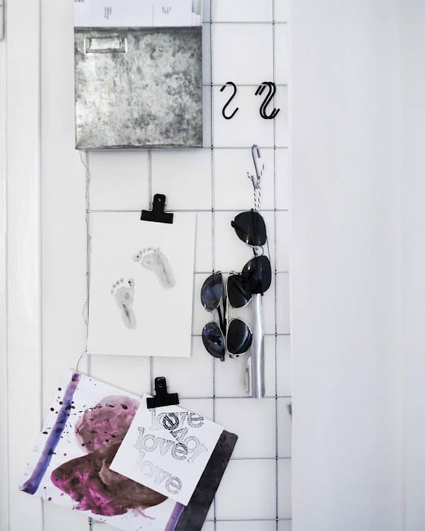 Pictures, notes and sunglasses being displayed on a wire grid on the wall