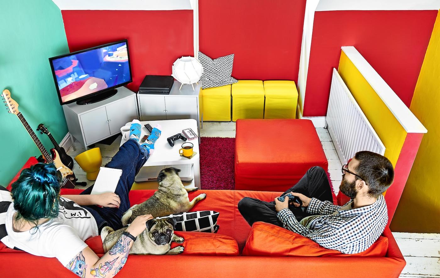 Pièce décorée de couleurs vives, avec canapé et console de jeux.