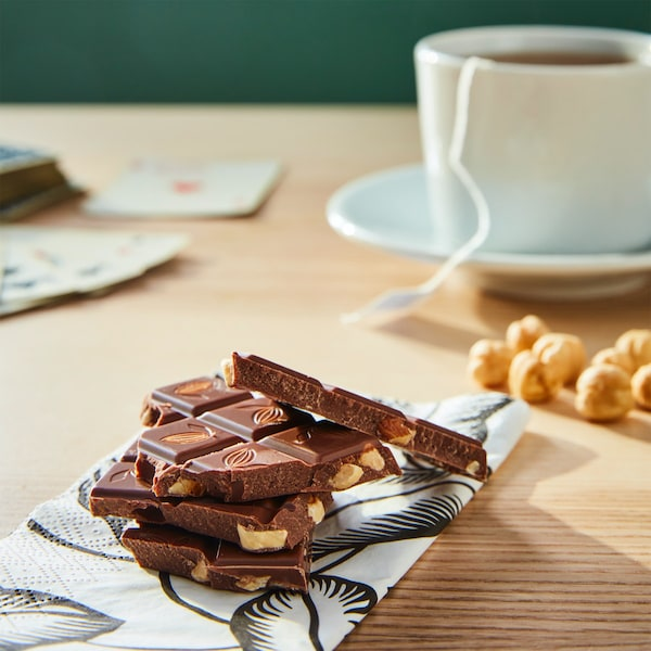 Pieces of CHOKLAD NÖT milk chocolate bar with hazelnuts on a piece of paper with playing cards, a cup of tea with a teabag and some hazelnuts in the background.