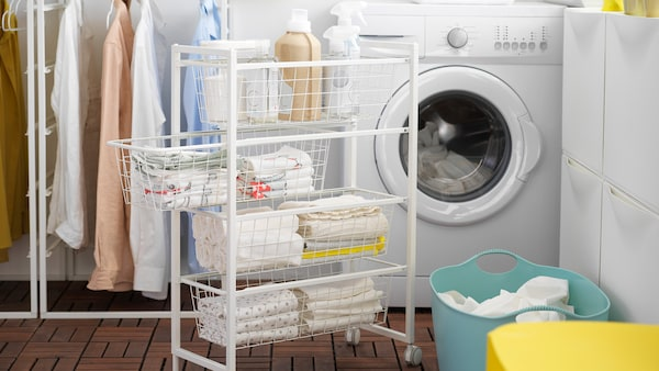 Pieces of cloths and bottles in a JONAXEL storage combination in front of a rack of clothes and washing machine.