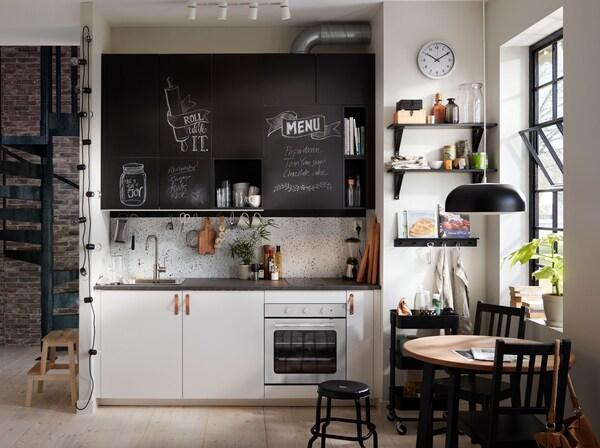 Pieni mustavalkoinen bistrotyylinen ranskalainen keittiö, jossa liitutauluovet. Keittiökaapeissa on nahkaiset vetimet.