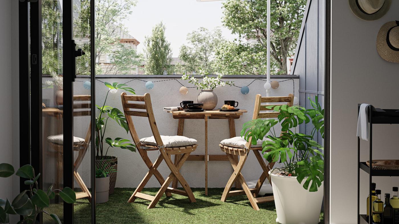 Pieni parveke, jolla puinen pöytä ja kaksi tuolia.