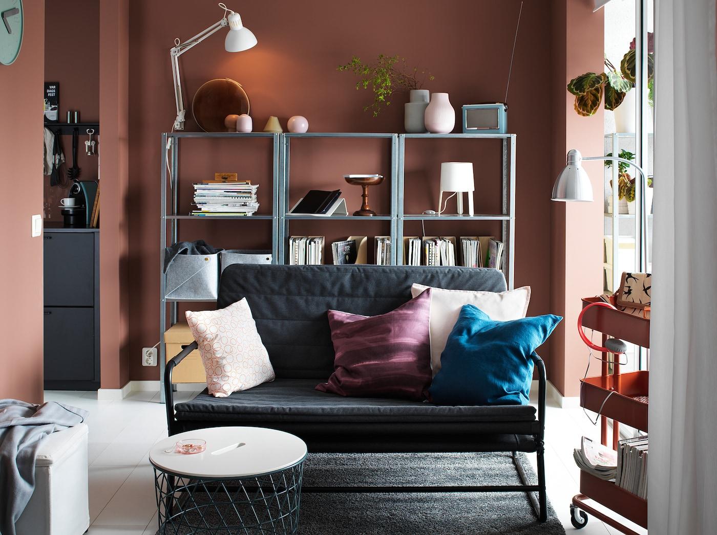 Pieni tummanharmaa-musta sohva olohuoneessa, jossa on punaruskeat seinät ja metallinen kirjahylly takaseinällä.