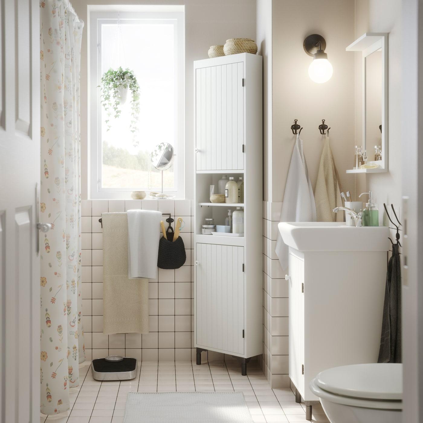 Pieni valkoinen kylpyhuone, jossa kulmakaappi, allaskaappi ja peili, jossa hylly.